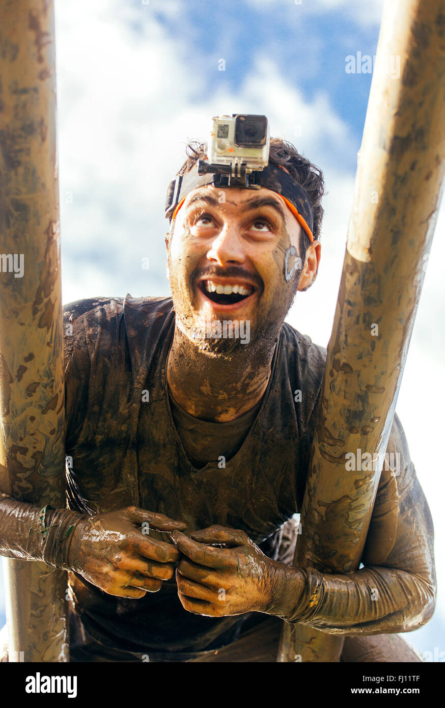 Participants in extreme obstacle race climbing on monkey bars - Stock Image