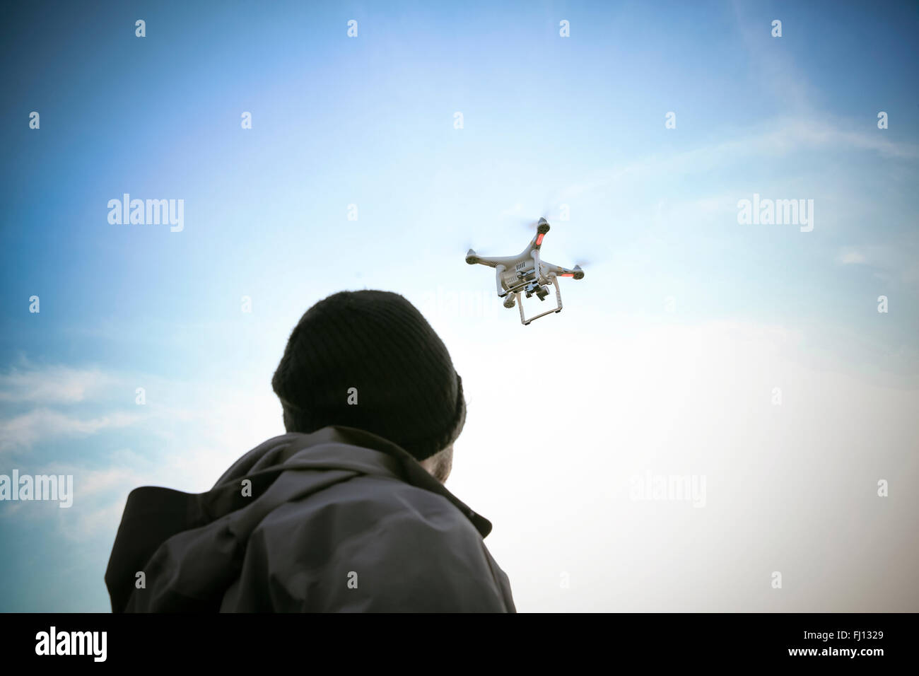 Back view of man flying drone - Stock Image