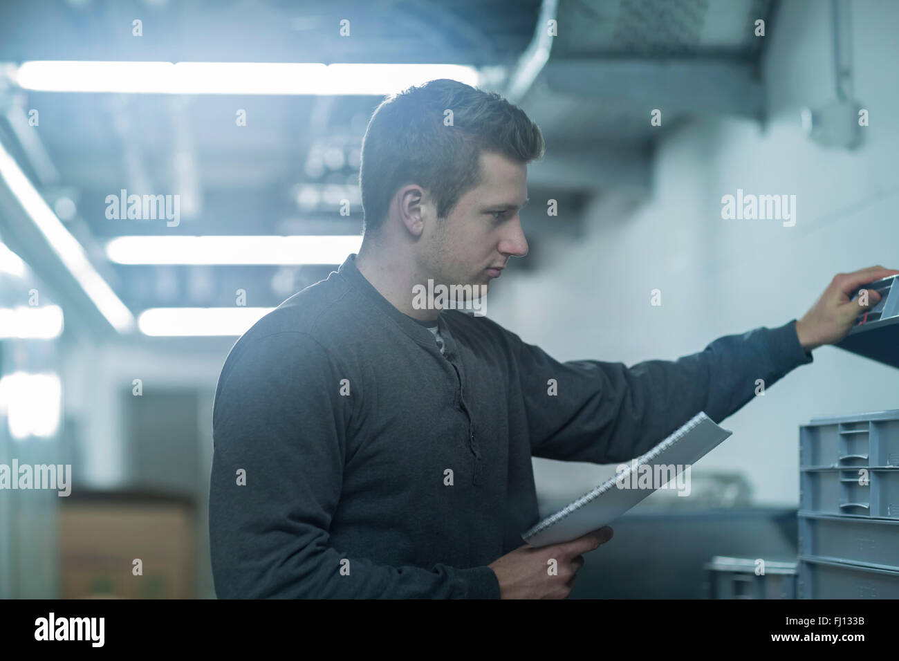 Young man working in technical room - Stock Image