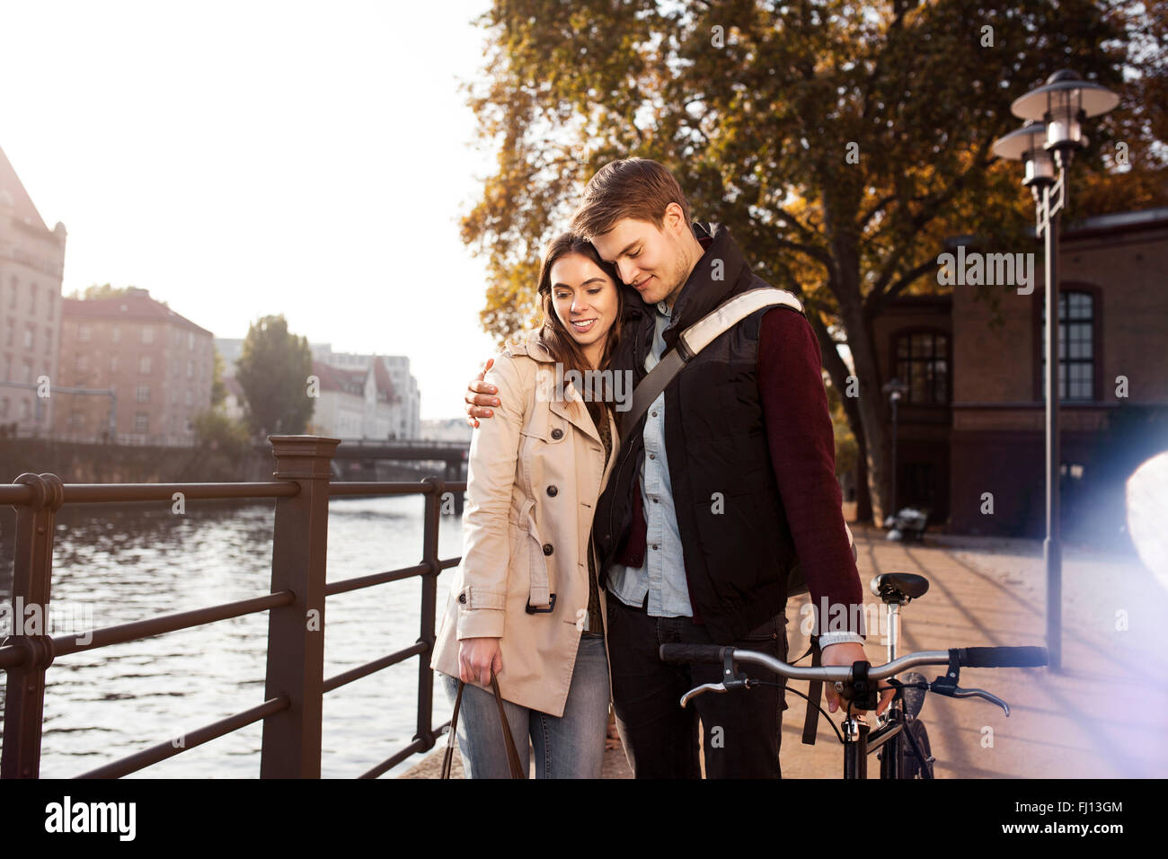 Germany, Berlin, young couple hugging at River Spree Stock Photo