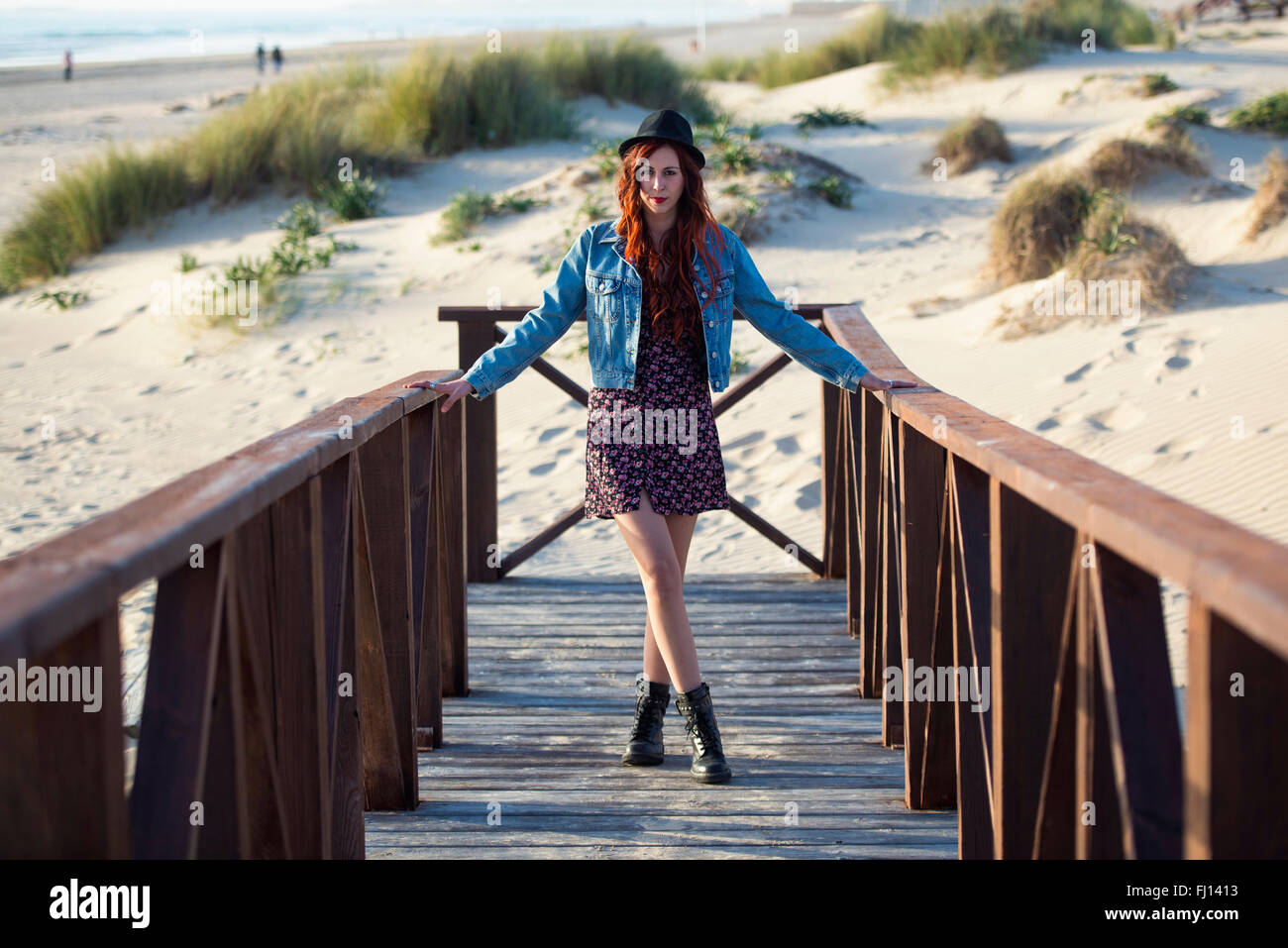 Spain, Cadiz, portrait of young redheaded woman standing on boardwalk at the beach - Stock Image