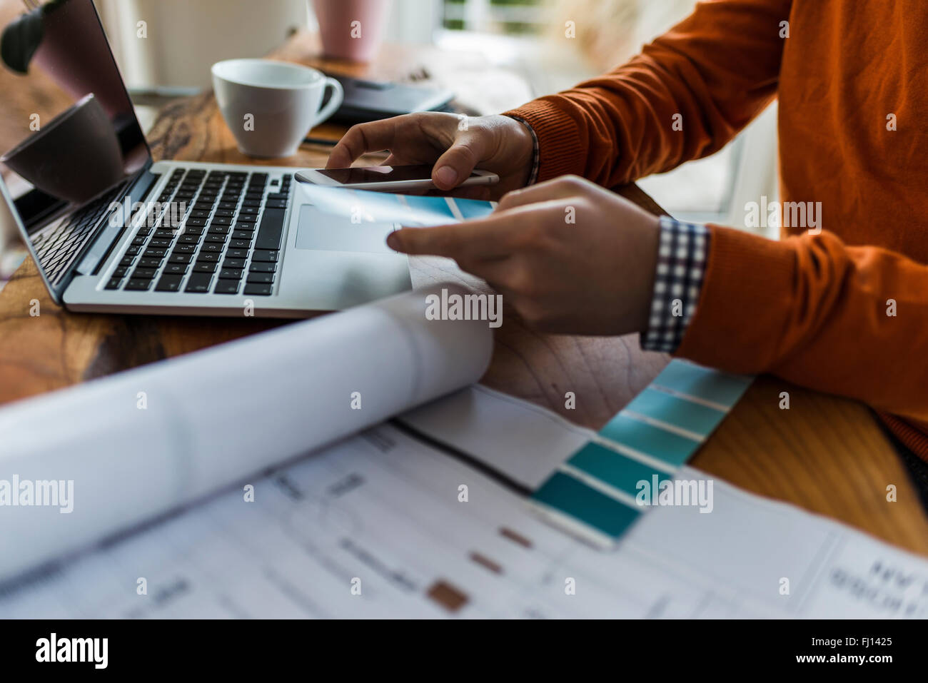 Close-up of man with cell phone, laptop and color samples at desk - Stock Image
