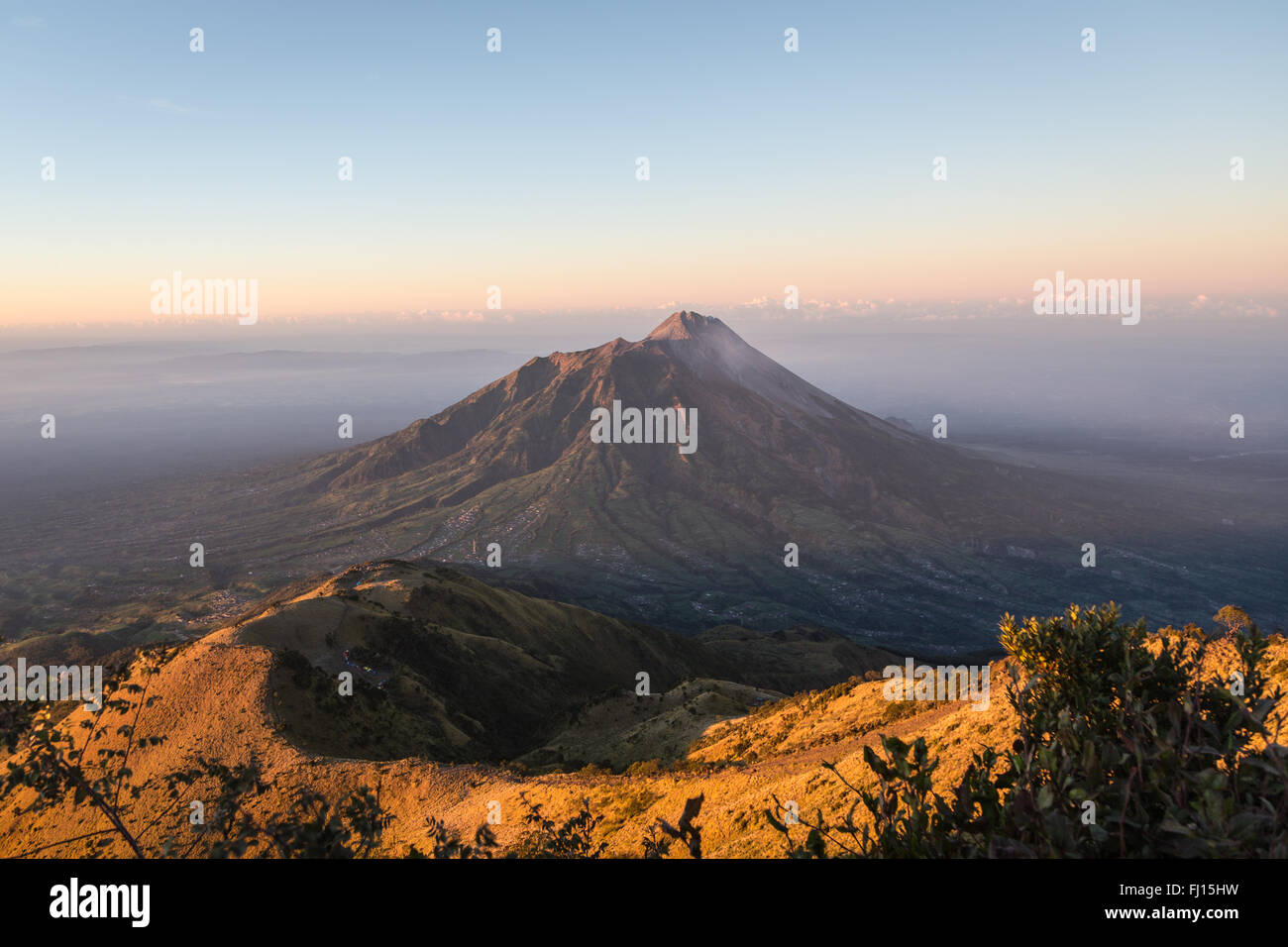 Stunning sunrise over the Merapi volcano and the countryside around Yogyakarta in entral Java in Indonesia from - Stock Image