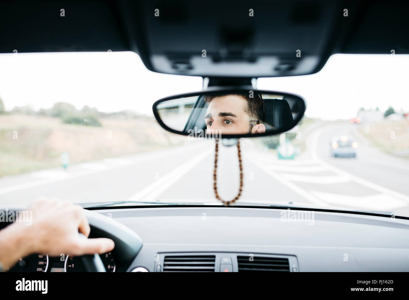 Young man driving a car, close up of rear mirror - Stock Image