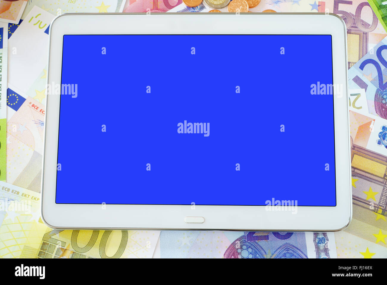 Tablet PC with blue blank touchscreen on a background of Euro banknotes - Stock Image