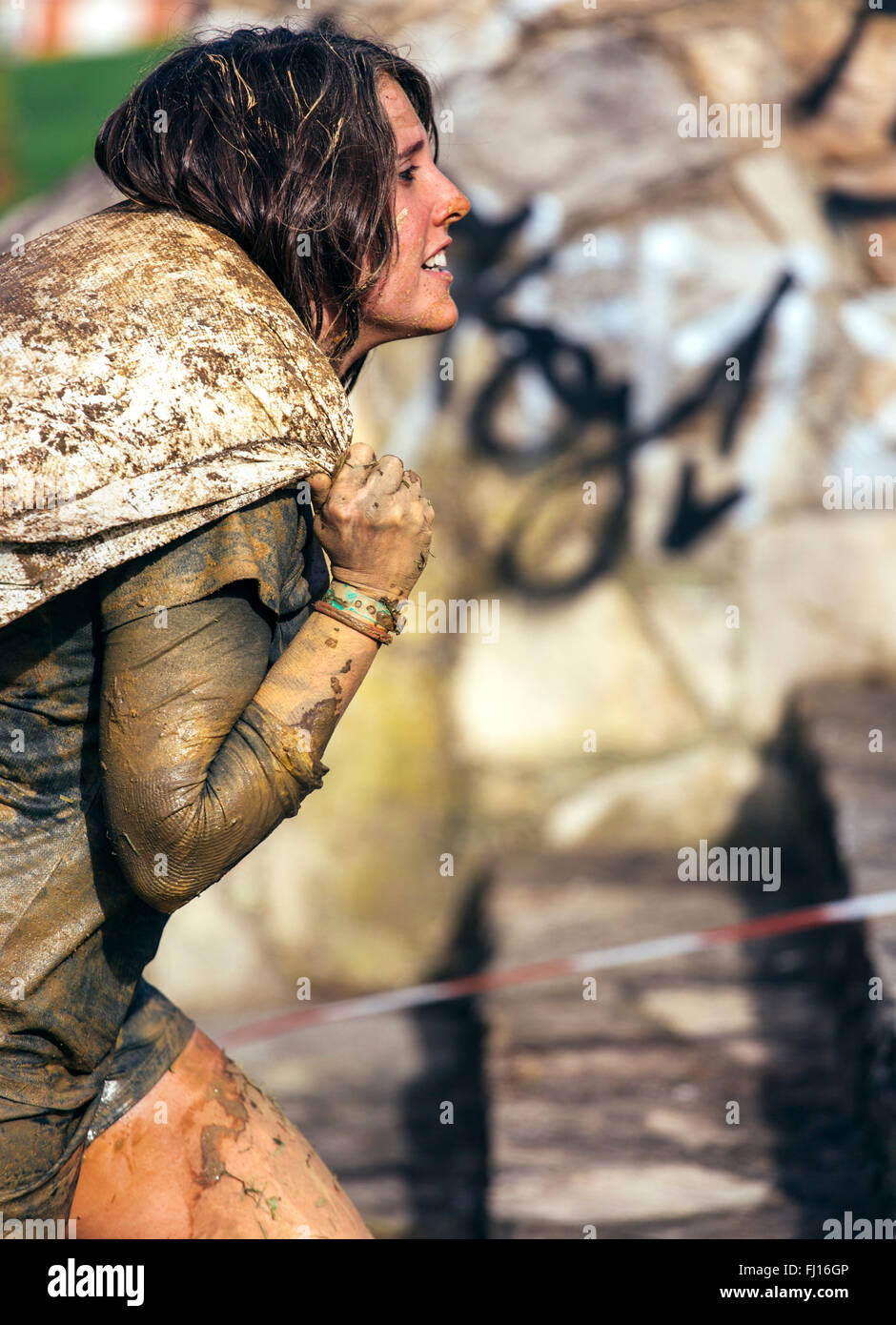 Participant in extreme obstacle race carrying sandbags - Stock Image