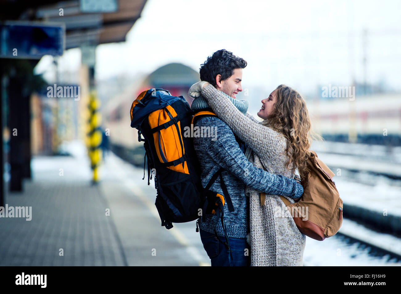 Smiling young couple embracing on station platform - Stock Image