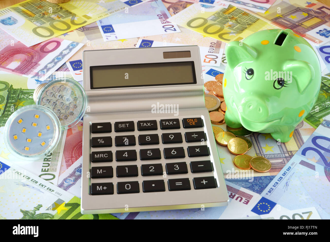 Pocket calculator with blank display, LED lamps, green piggy bank on a background made of euro banknotes and coins - Stock Image