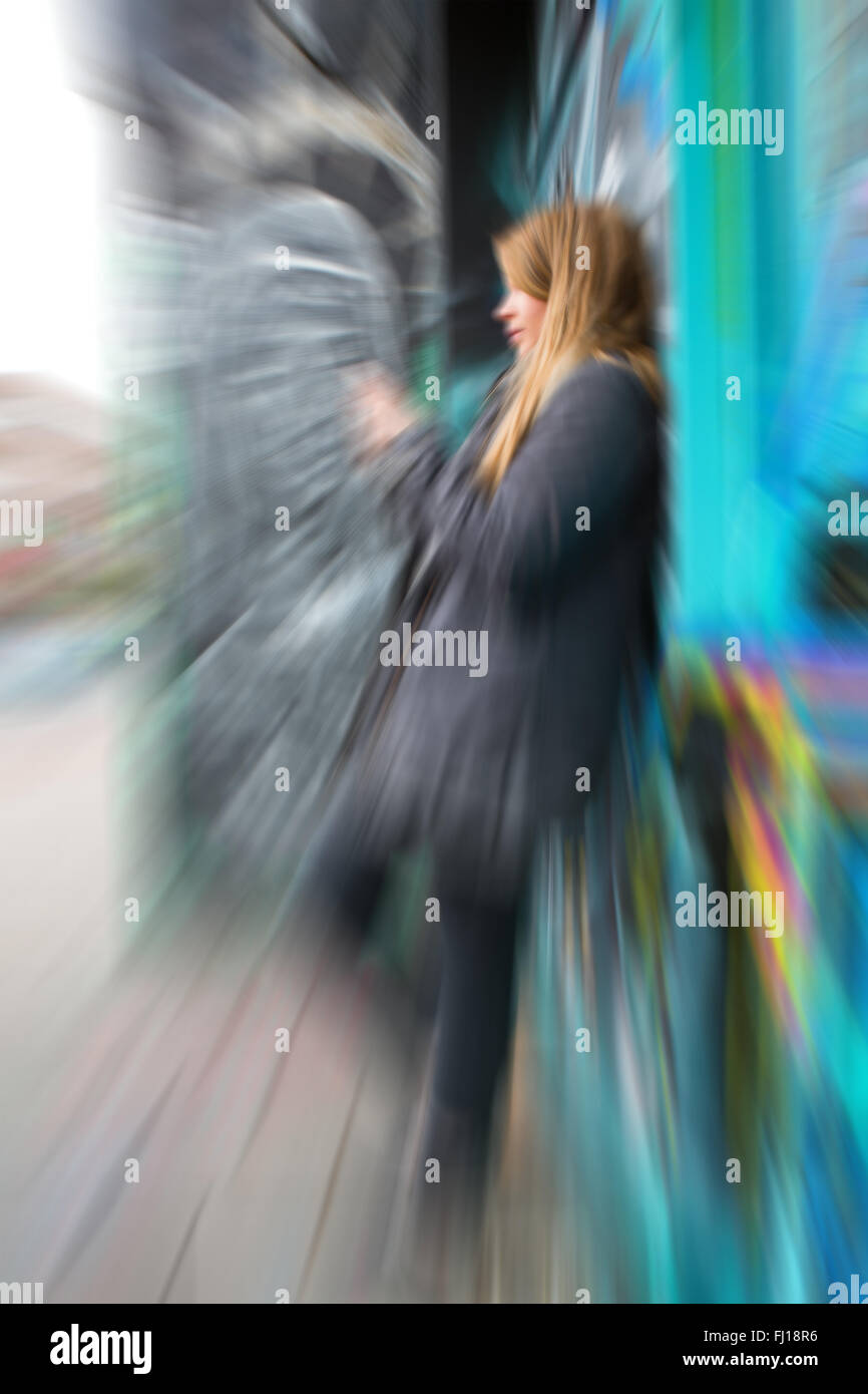 young girl text iphone smart phone graffiti city - Stock Image