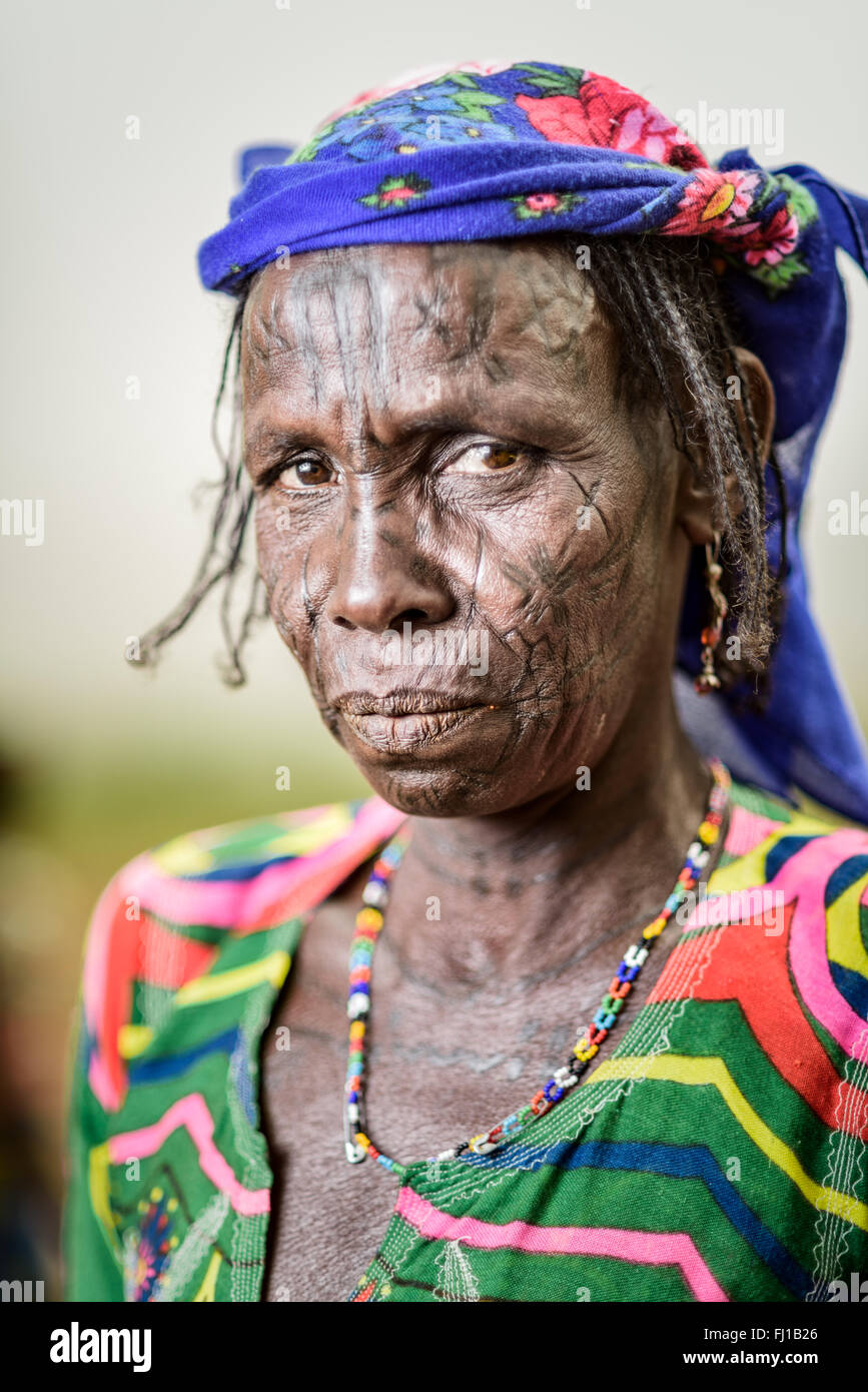 Portrait of a Mbororo woman with scars on her face dressed in a very colourful outfit. Stock Photo