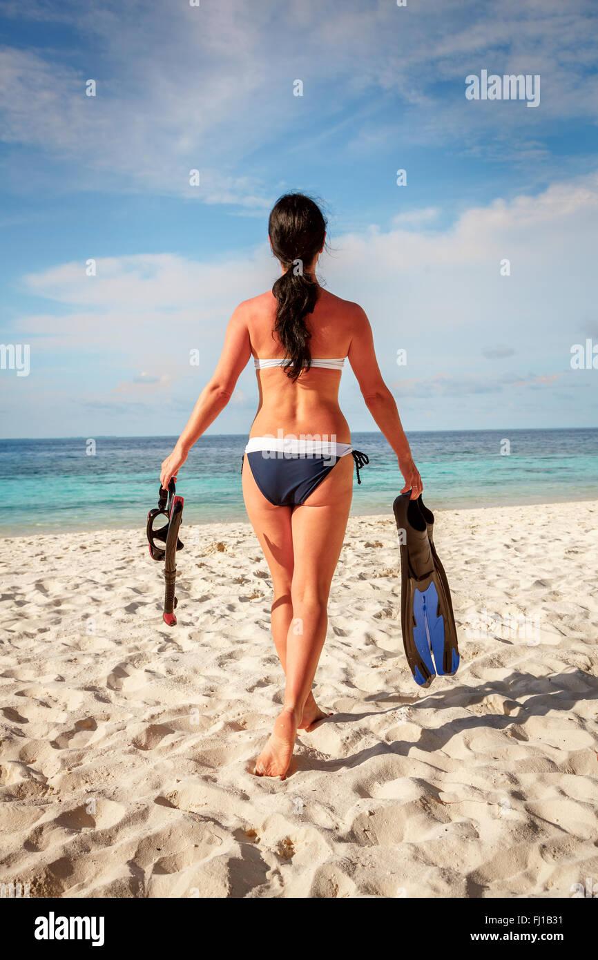 Girl in bikini with snorkeling gear on the beach Maldives. - Stock Image