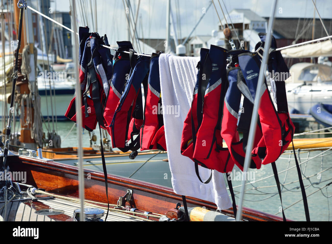 life jackets strung out to dry on yacht in Cowes Marina, Isle of Wight - Stock Image