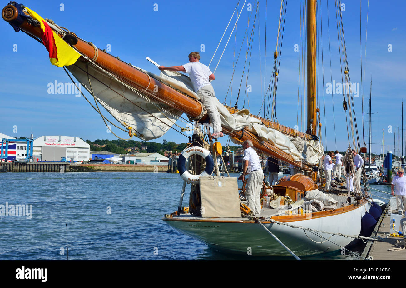 Crew of large wooden classic yacht furls the huge mainsail to the large wooden boom following racing. Cowes Harbour, - Stock Image