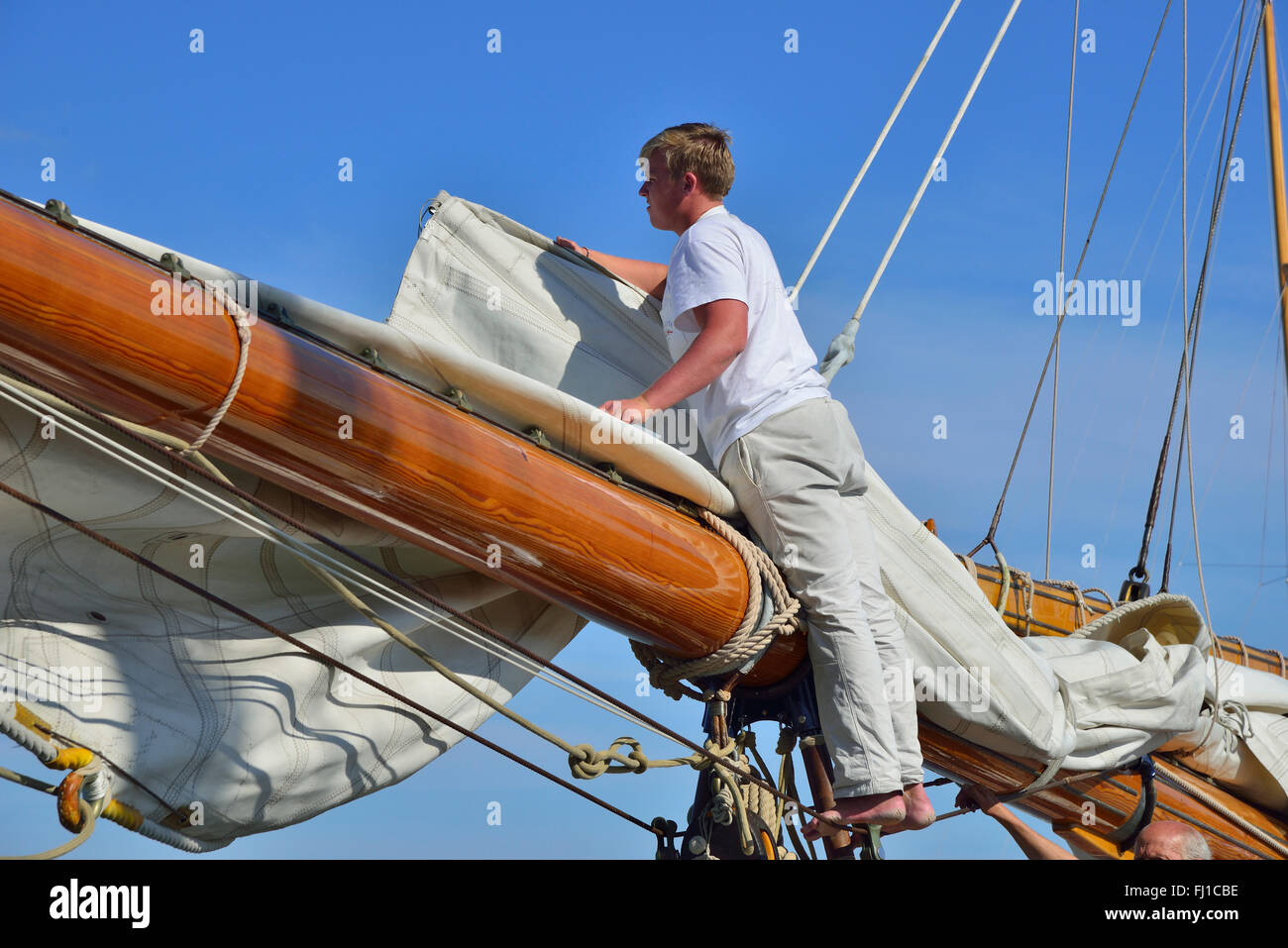 Crew of large wooden classic yacht furls the huge mainsail to the large wooden boom in Cowes Harbour, Cowes, Isle - Stock Image
