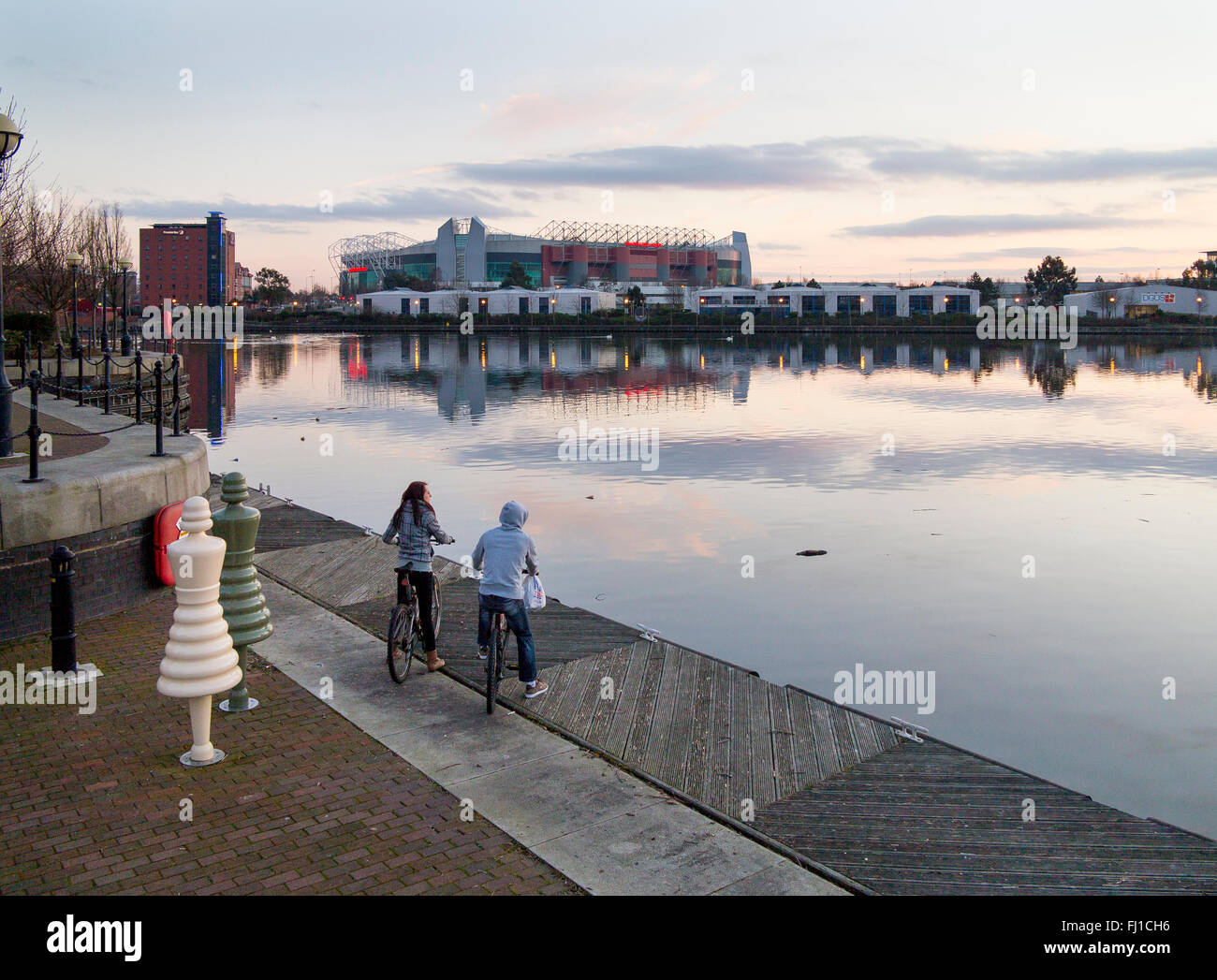 Two youths on bikes, a boy and a girl, view Old Trafford stadium, home of Manchester United Football Club, from - Stock Image