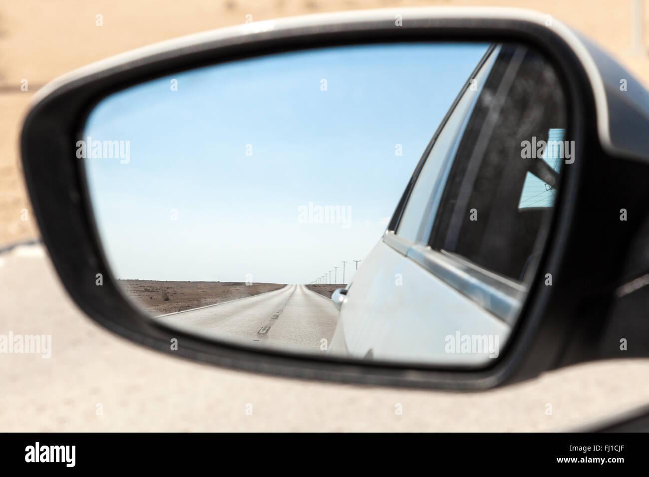 Desert road in Qatar in rear view mirror - Stock Image