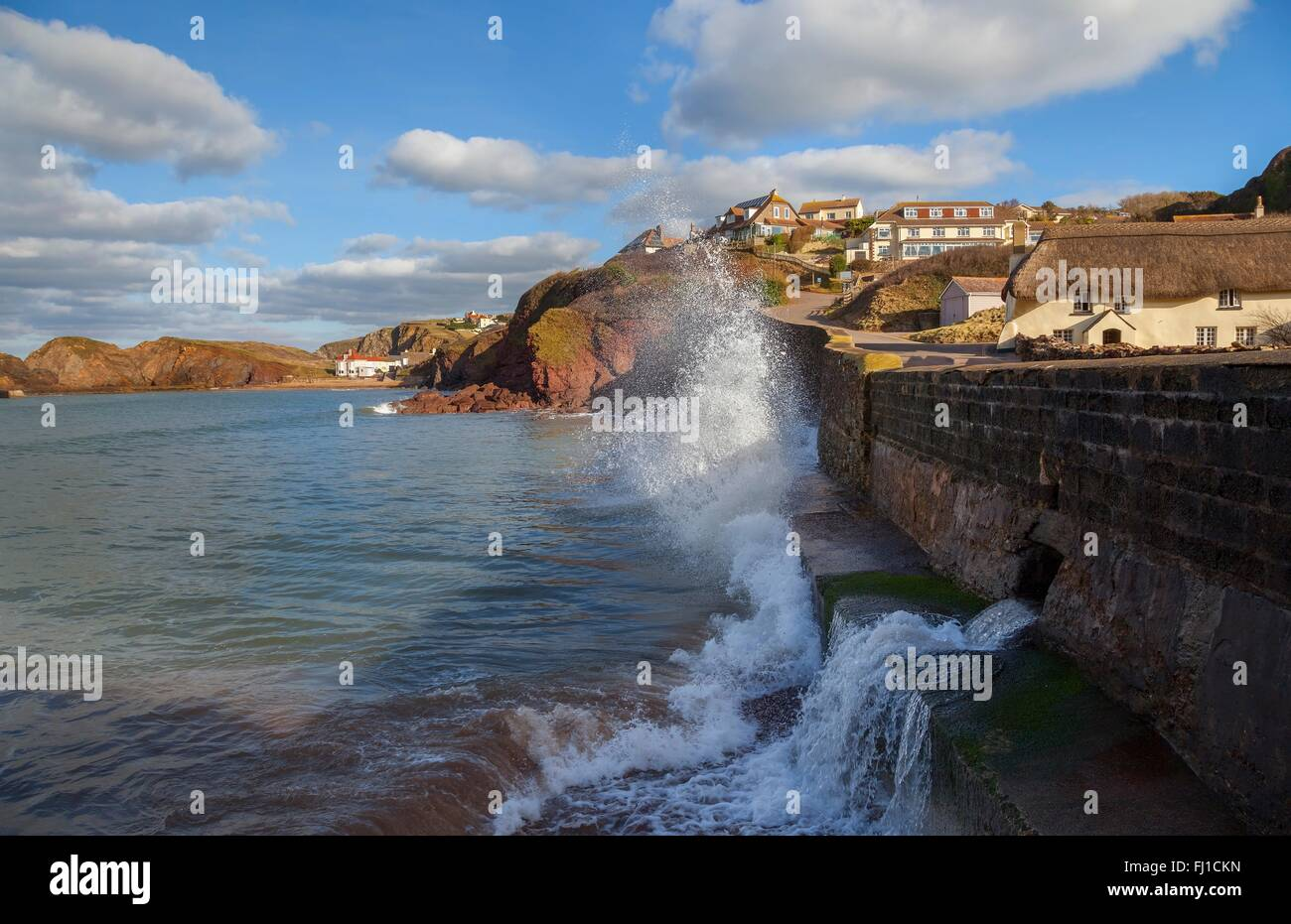 Waves crashing against the sea wall at Hope Cove, Devon, England - Stock Image