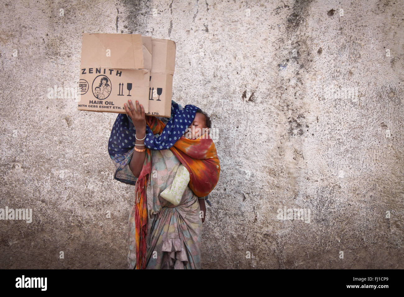 A woman beggar in the streets of Harar is hiding her face with a piece of cardboard and carrying her sleeping baby - Stock Image