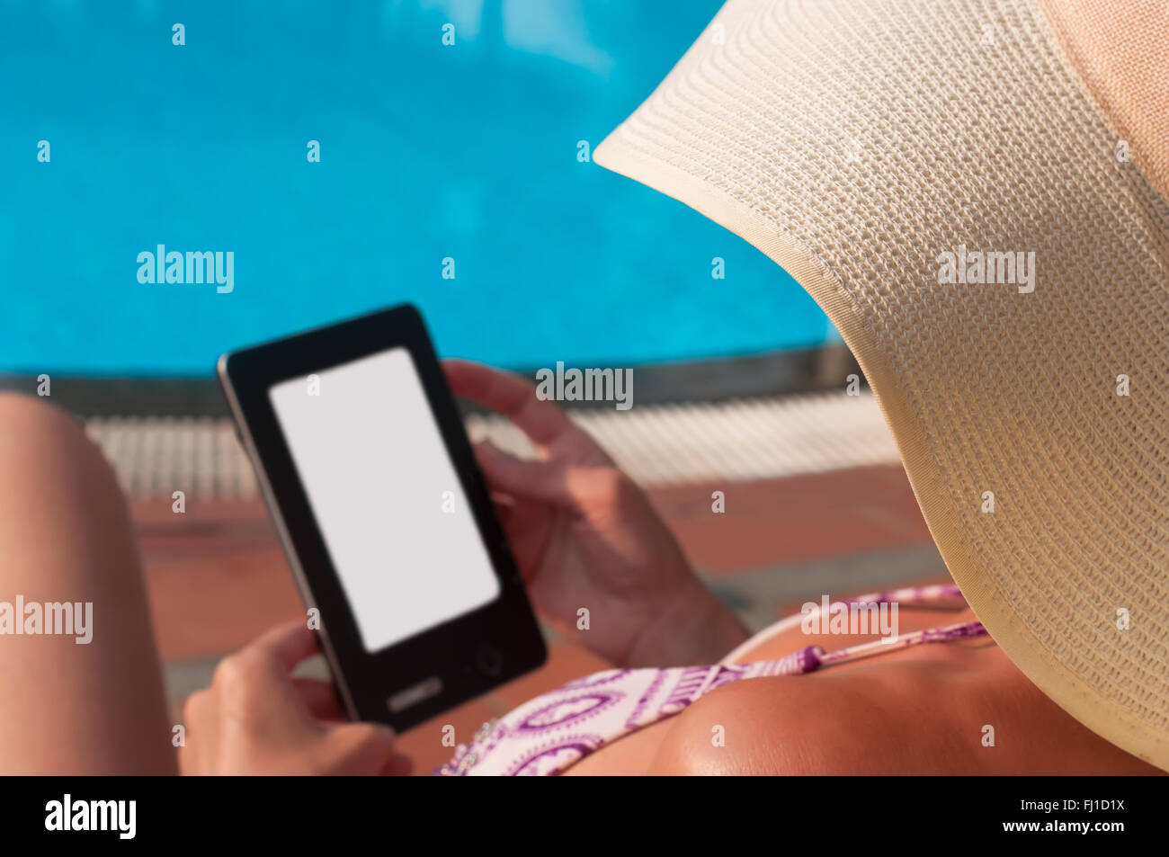 Woman  with hat reading e-book closed to swimming pool - Stock Image