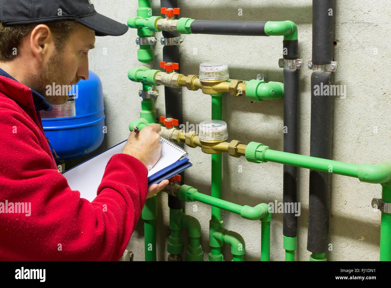 plumber at work making the consumption metering - Stock Image