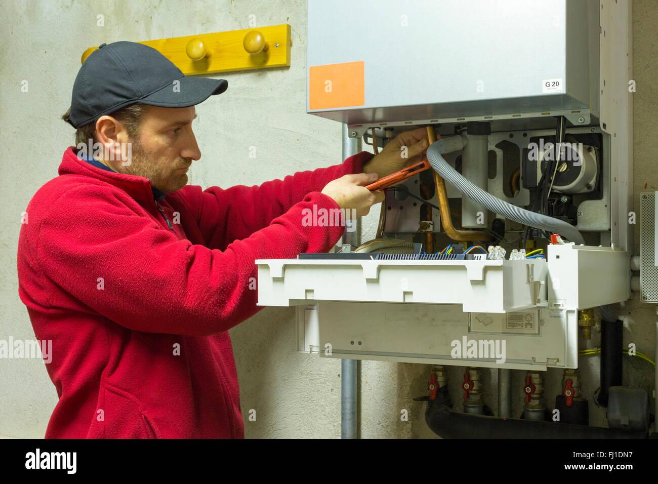 plumber repairing a condensing boiler in the boiler room - Stock Image