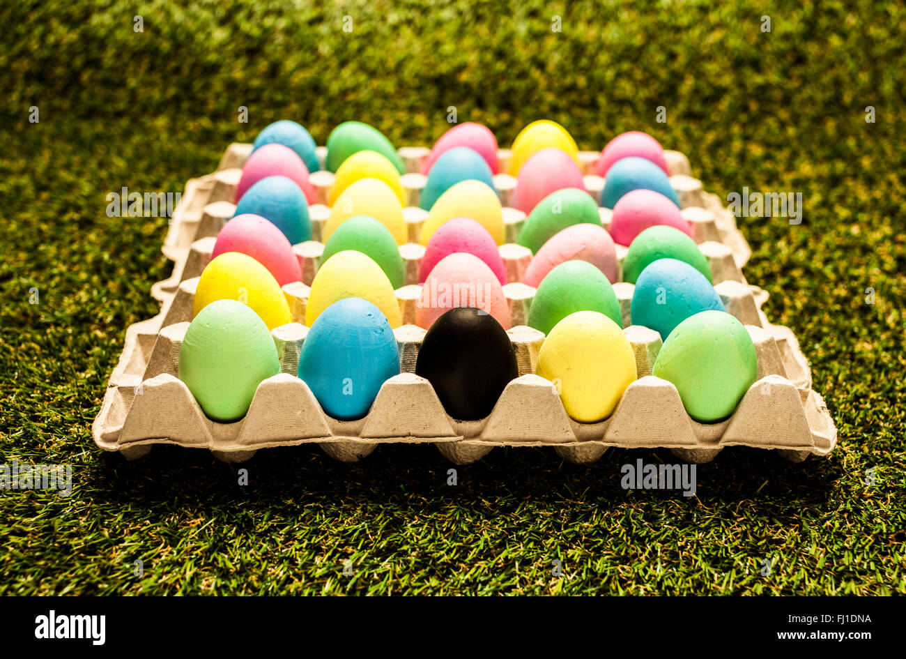 colored easter eggs in carton with one black egg Stock Photo