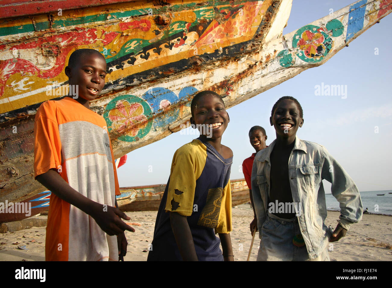 Kids children posing on the beach of Joal Fadiouth , Senegal , in front of a traditional painted boat canoe - Stock Image