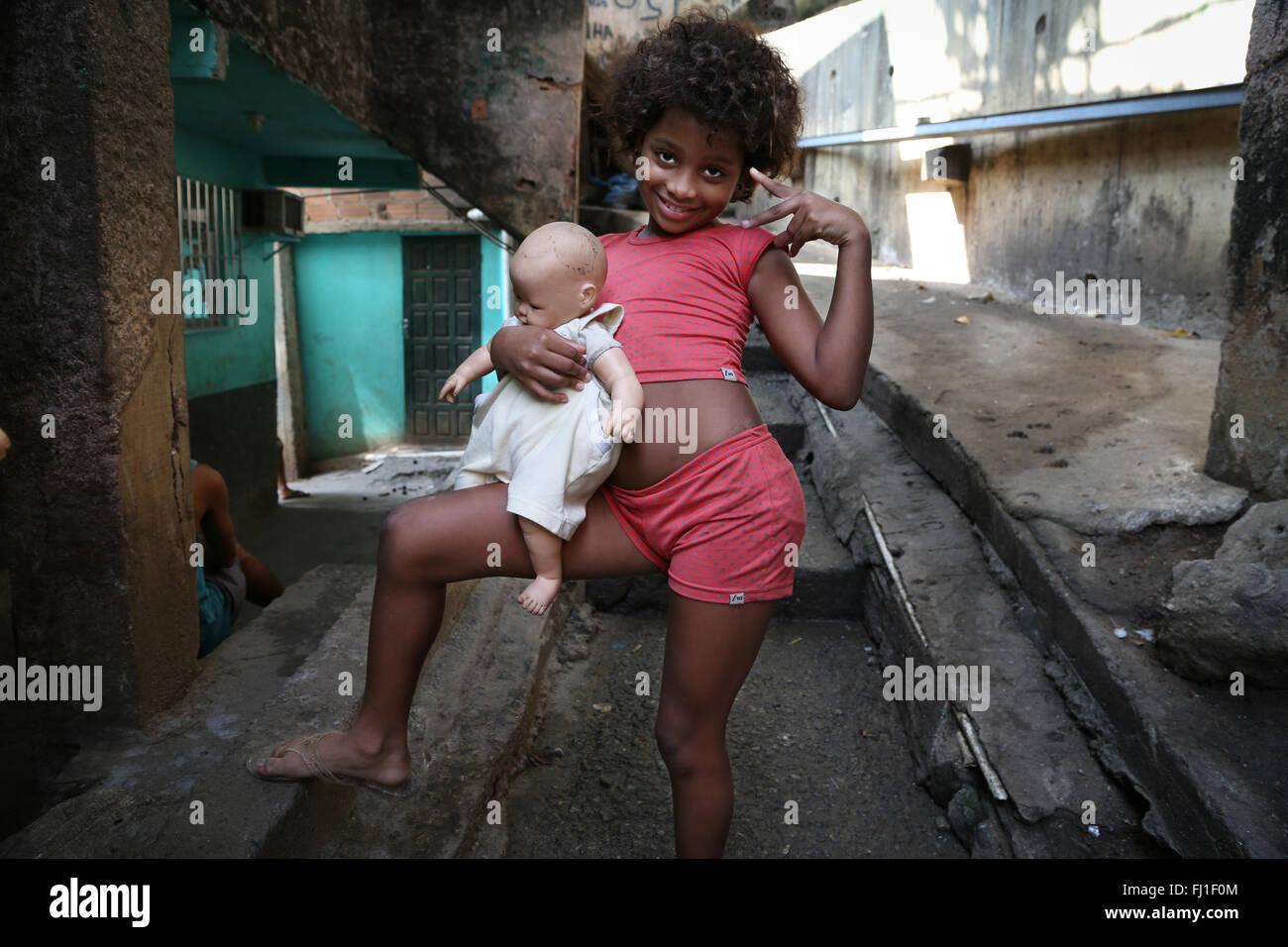 Girl with Baby Doll  living in favela de Rocinha, Rio de Janeiro, Brazil - Stock Image