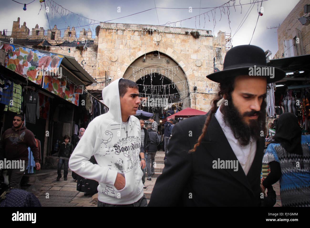 Arab man and Jewish traditional Ultra Orthodox Haredim man are walking togehter near Damascus gate , Jerusalem , - Stock Image