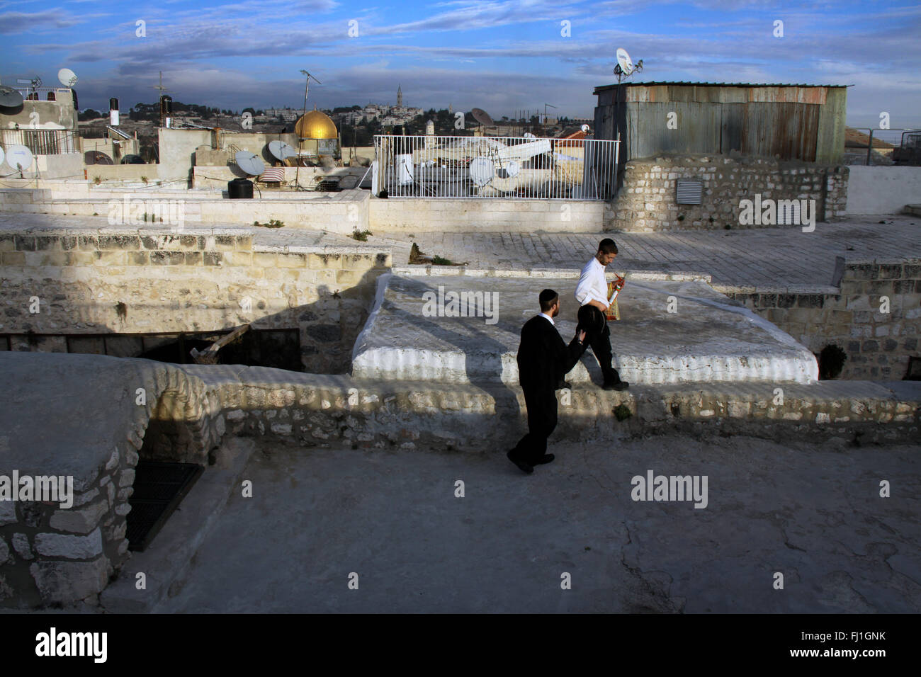 Two Jewish men walk by sunset on the roofs of Jerusalem old city , Al-Aqsa Mosque in the distance - Stock Image