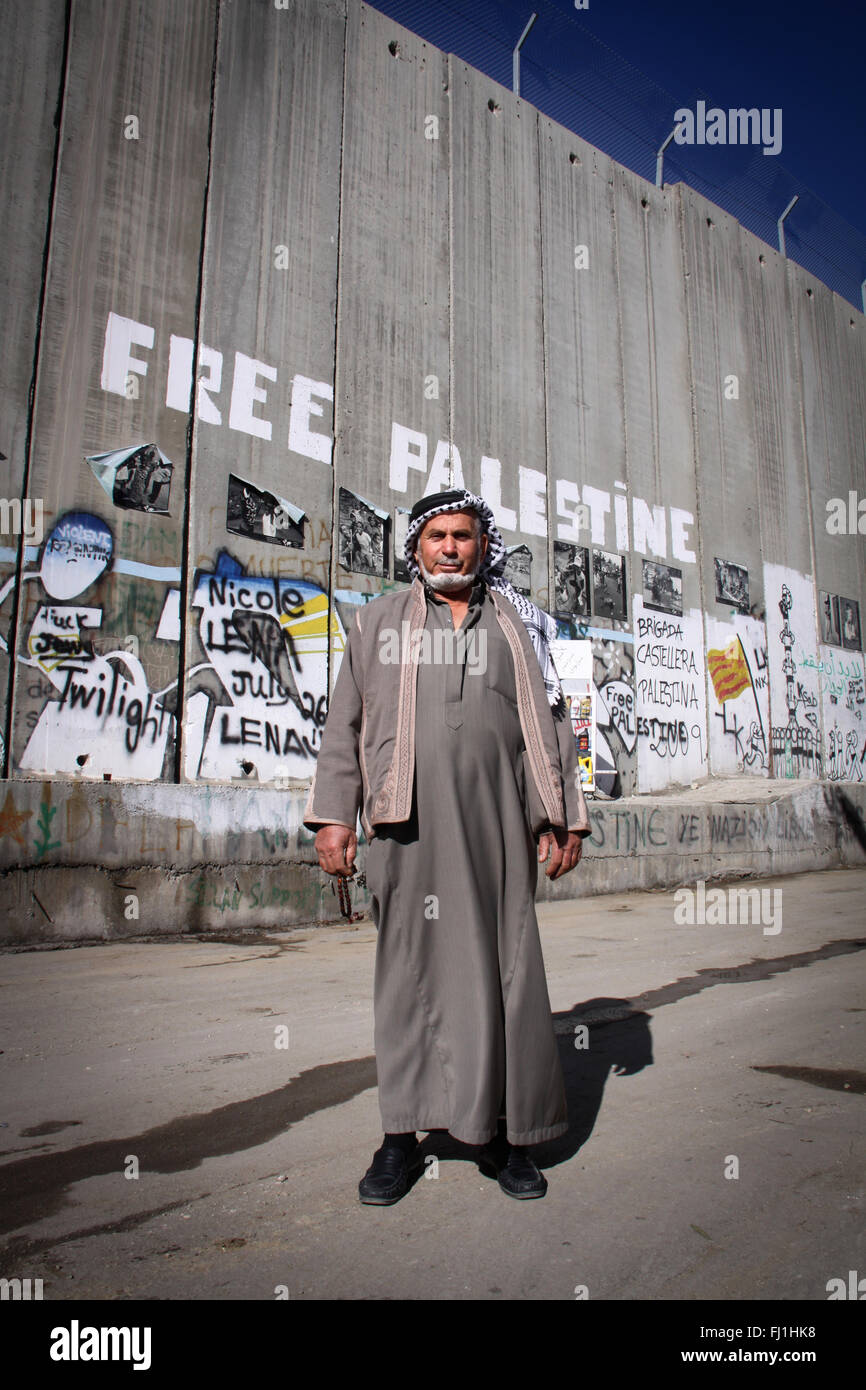 A Palestinian man stands at Bethlehem checkpoint in front of separation wall - Stock Image