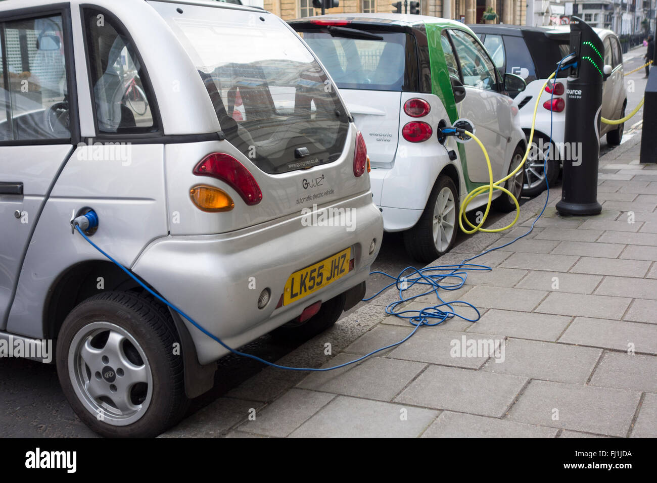 Electric vehicles plugged into charging points on a road in London, UK Stock Photo