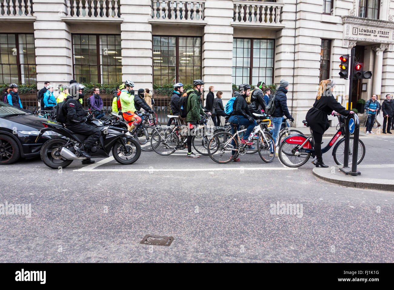 Cyclists waiting in bike box or Advanced Stop Line (ASL) at red traffic lights, Bank junction, London UK - Stock Image