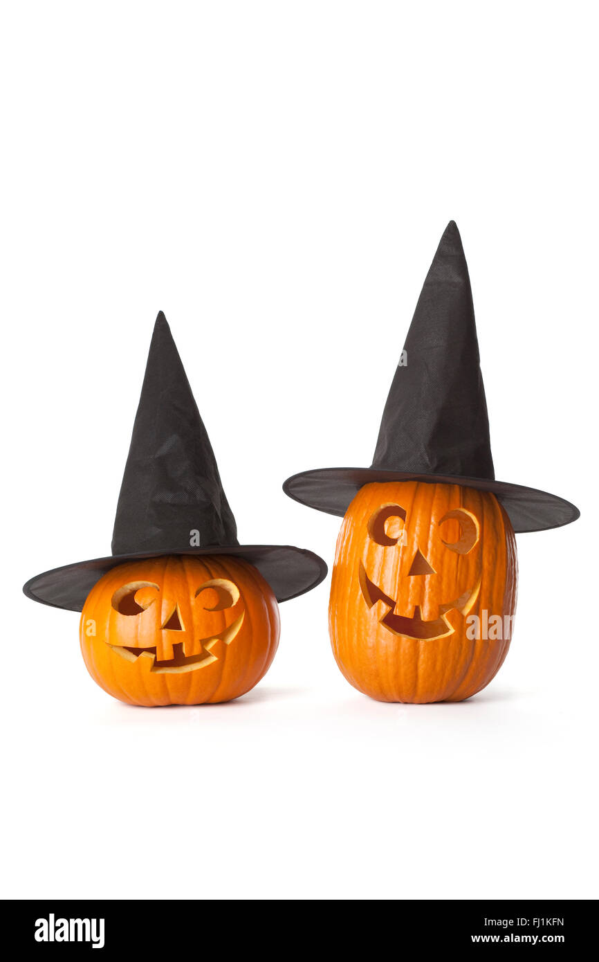 Two Halloween pumpkins with black hat on white background - Stock Image