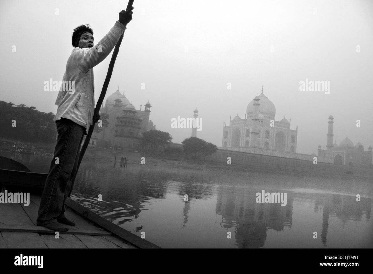 Man on boat on Yamuna river, with Taj Mahal, in the early morning, Agra India - Stock Image