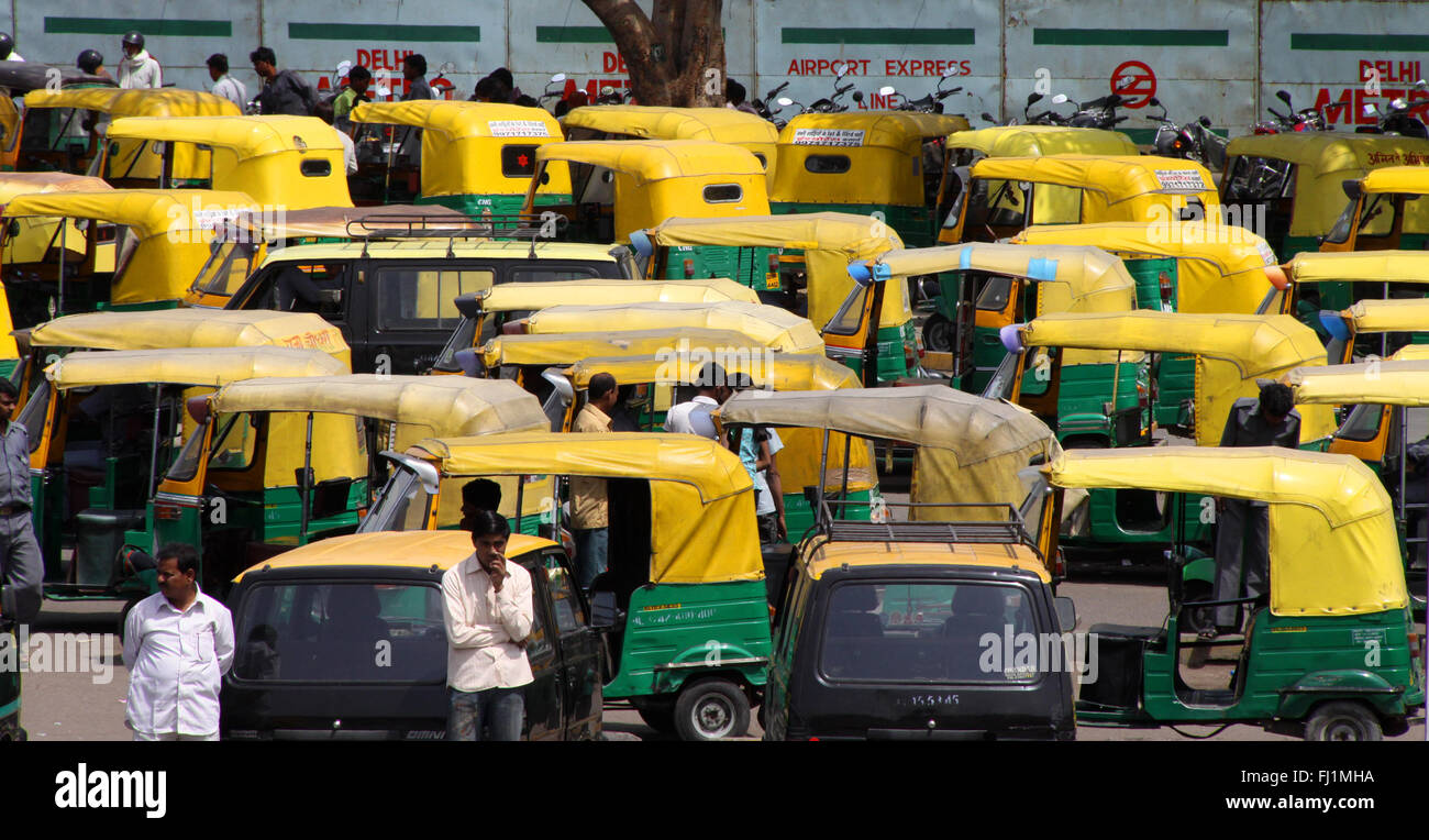 Parking of yellow and green rickshaws / taxi / cabs in Delhi, India - Stock Image