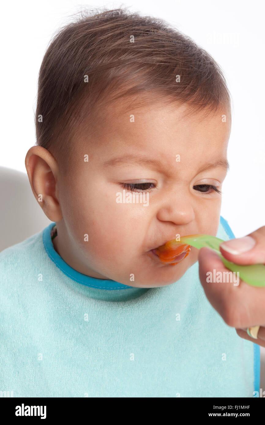 Baby girl is dislikes eating carrots on white background - Stock Image