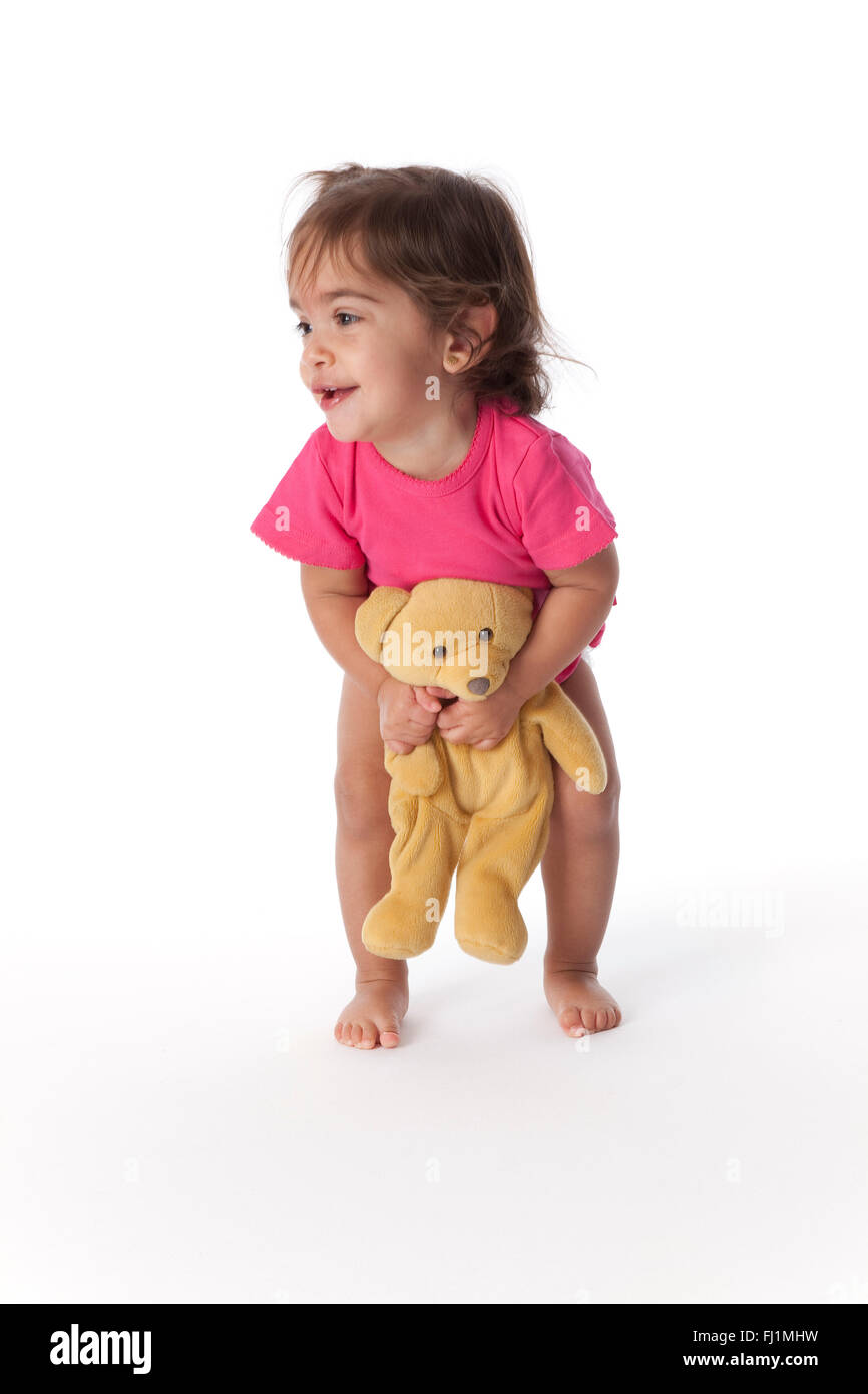 Baby girl having fun with a toy bear on white background - Stock Image