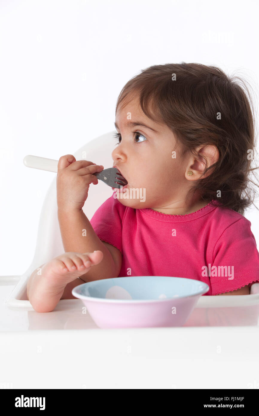 Baby girl is with a fork in her mouth on white background - Stock Image