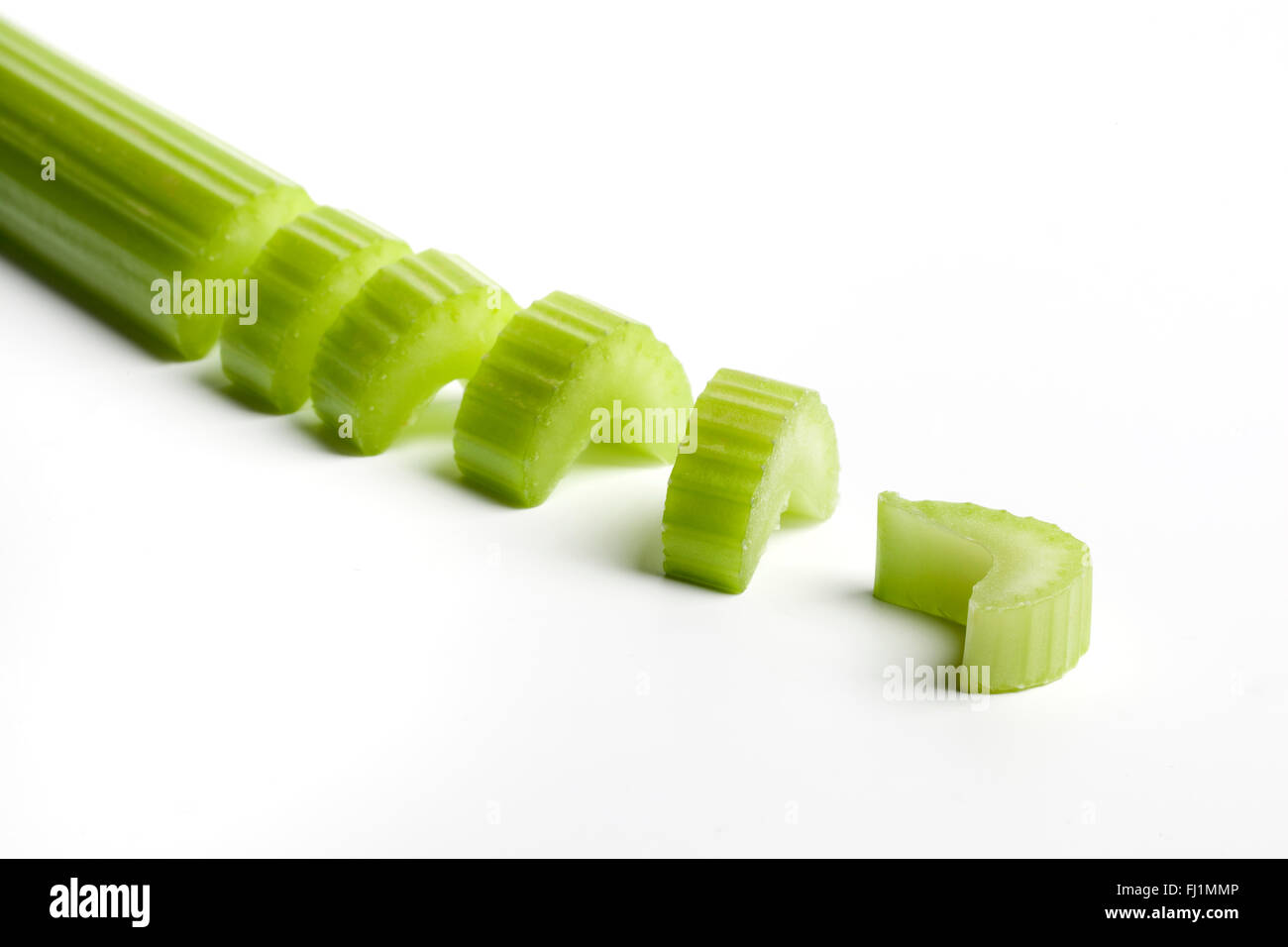 Fresh raw celery stem cut into pieces on white background - Stock Image