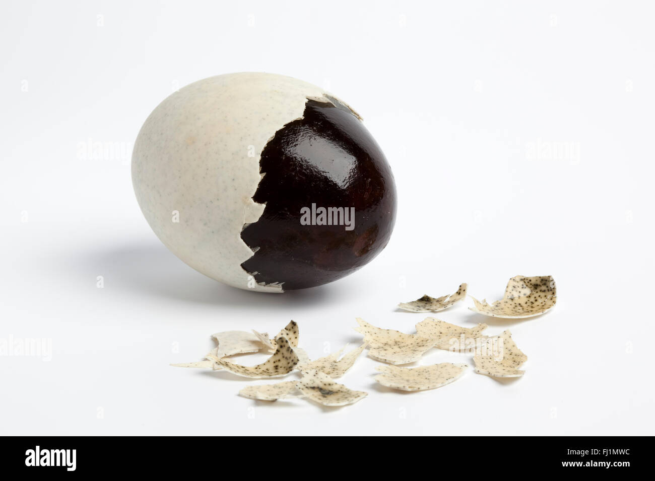Thousand years duck egg with partial peeled egg-shell on white background - Stock Image
