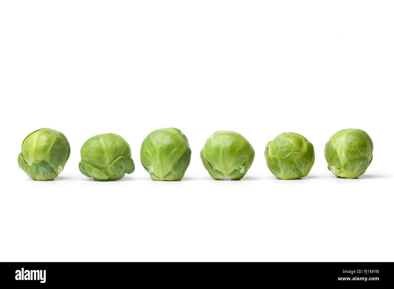 Row of fresh raw Brussel sprouts on white background - Stock Image
