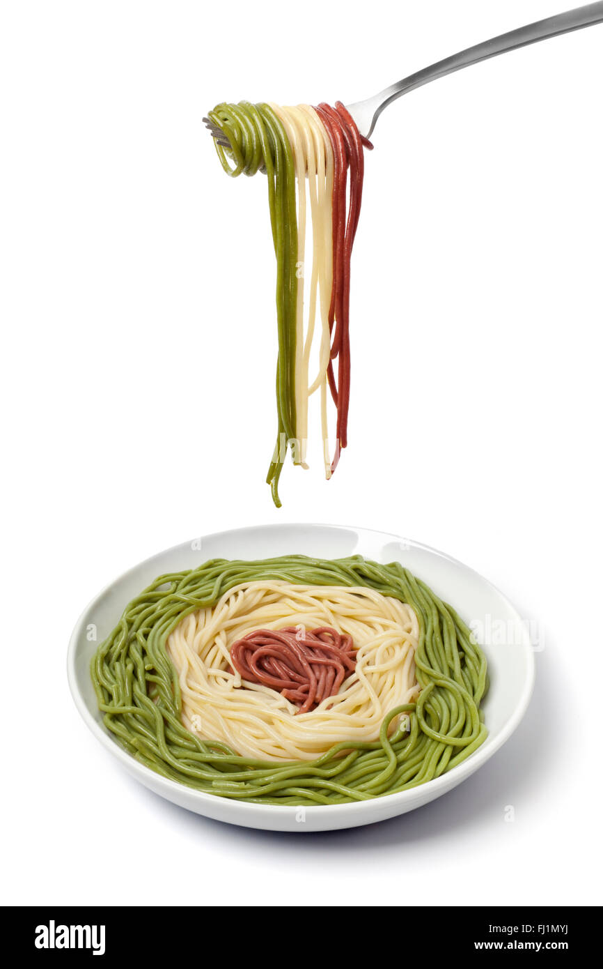 Dish and fork with cooked Spaghetti tricolore on white background - Stock Image