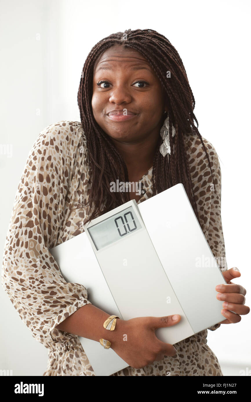 Teenage girl with a funny expression carrying a scale on white background - Stock Image