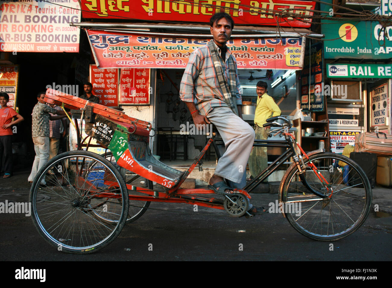 Cyclo Rickshaw driver in a street in Delhi, India - Stock Image