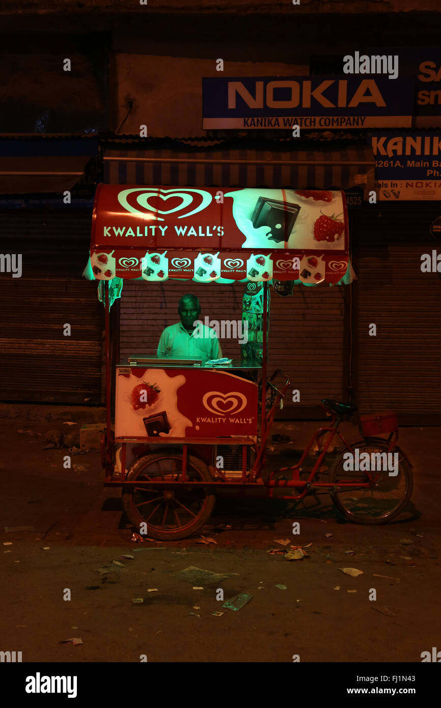Man sells ice cream in a street of Delhi at night , India Stock Photo