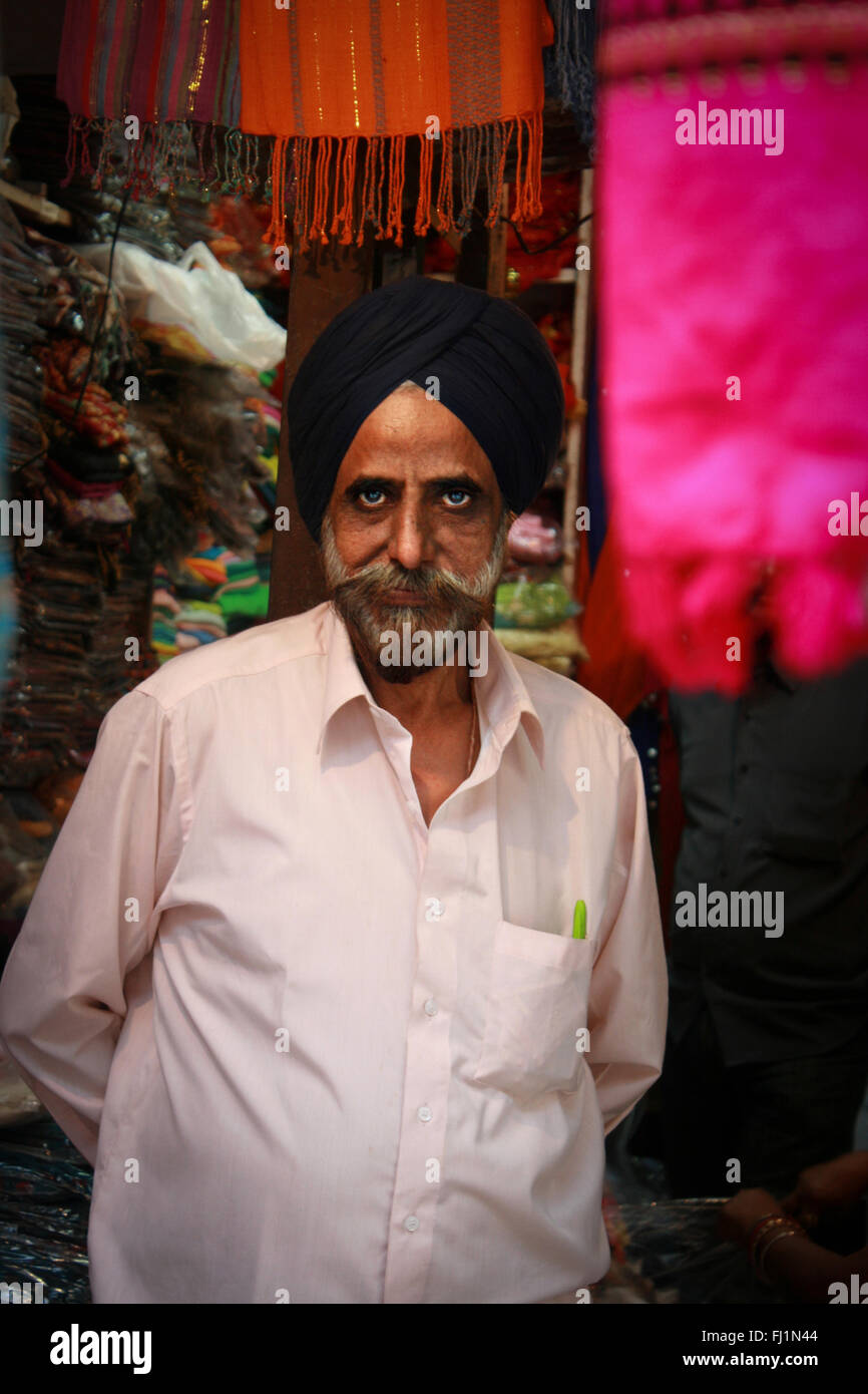 Sikh man selling clothes in shop in Delhi, India Stock Photo