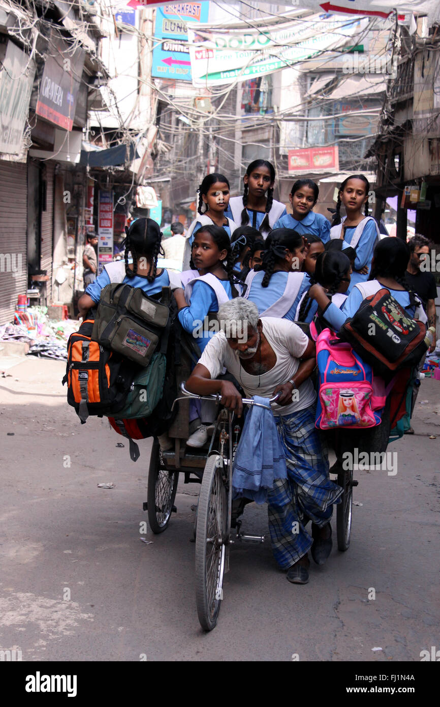 Man working hard to bring Indian kids to school in the morning in Delhi - Stock Image