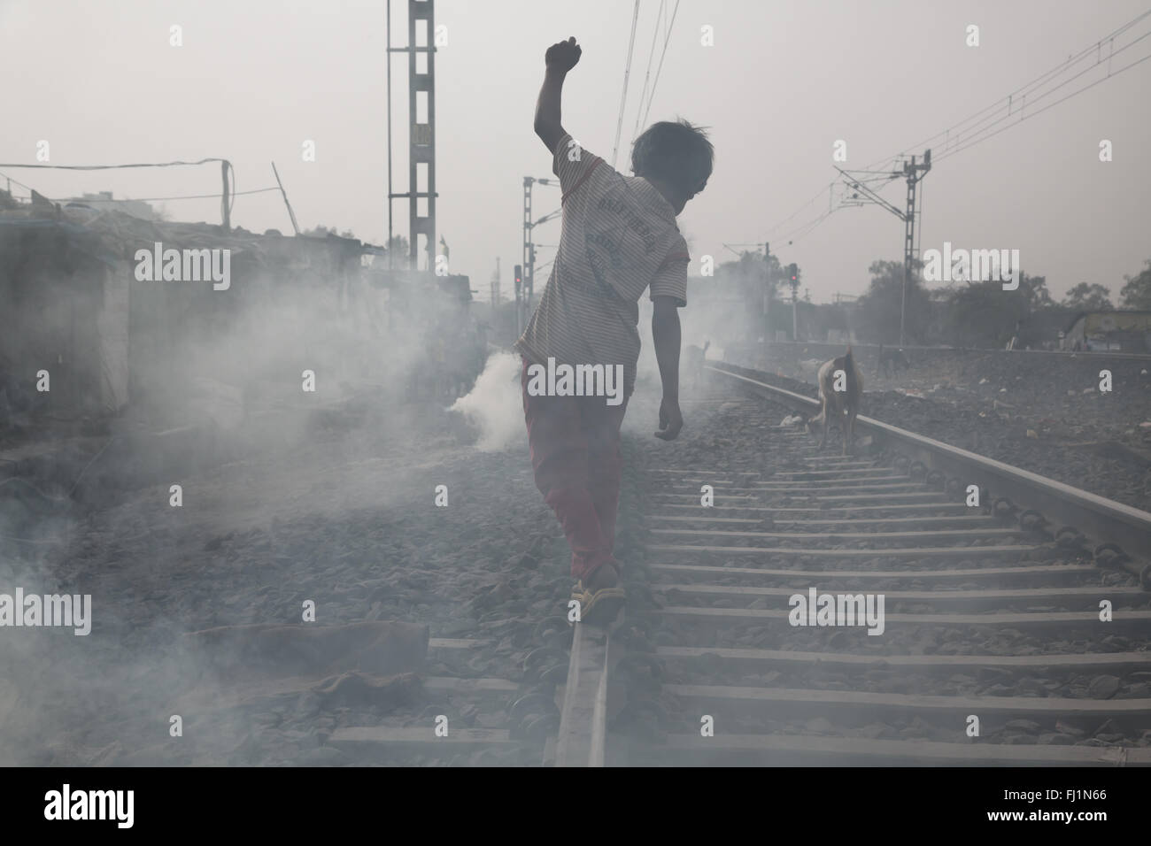 A kid is walking along train rails in Bhopal , India - Stock Image