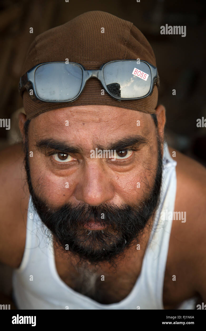 Indian man with beard and sunglasses with sticker 'boss' written , Bhopal , India - Stock Image